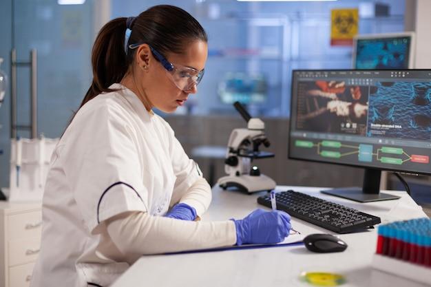 Specialista in microbiologia che analizza il campione di dna al microscopio