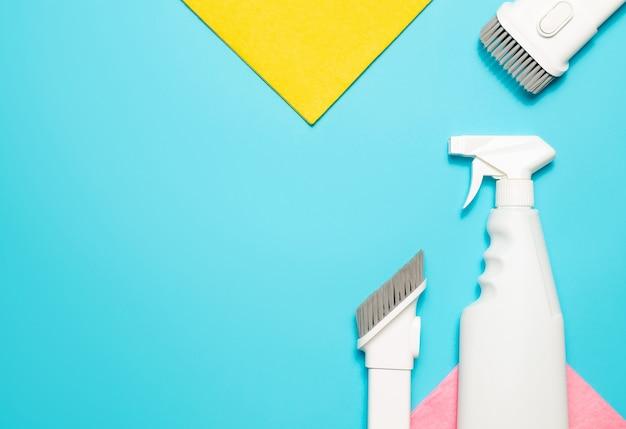 Panno in microfibra, accessori per aspirapolvere e detergente spray su sfondo blu, vista dall'alto, copia dello spazio. prodotti per la pulizia.