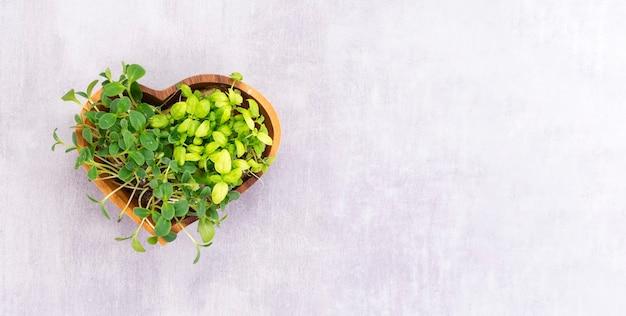 Microgreens in un piatto di legno a forma di cuore sul tavolo, concetto di cibo sano.