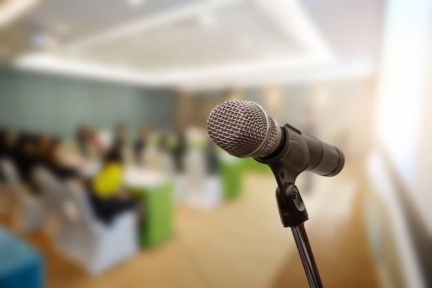 Microfono sopra il forum aziendale offuscata riunione o conferenza formazione apprendimento coaching room concept, sfondo sfocato.