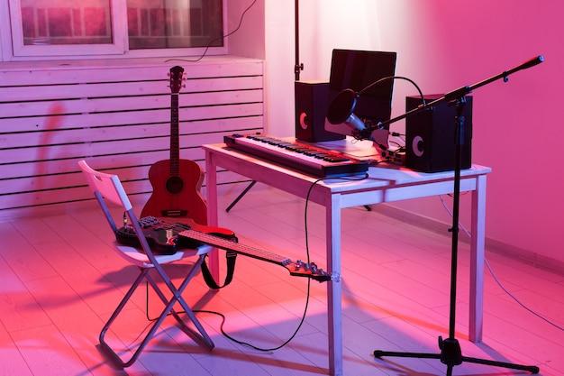 Microfono, computer e attrezzature musicali chitarre e sfondo di pianoforte. concetto di studio di registrazione domestico.