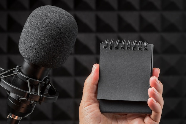 Microfono e taccuino del nero dello spazio della copia