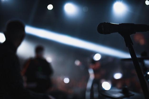 Microfono sul palco e sullo sfondo le persone sfocate brillano di luci