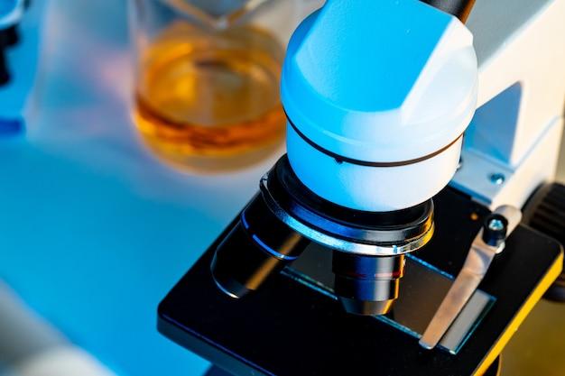 Lenti del microscopio su una fine dello scrittorio del laboratorio in su