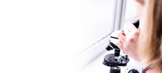 Il microscopio si trova su un tavolo bianco in un laboratorio di ricerca che conduce analisi e ricerche