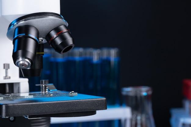 Il microscopio con le lenti si chiude su contro fondo scuro