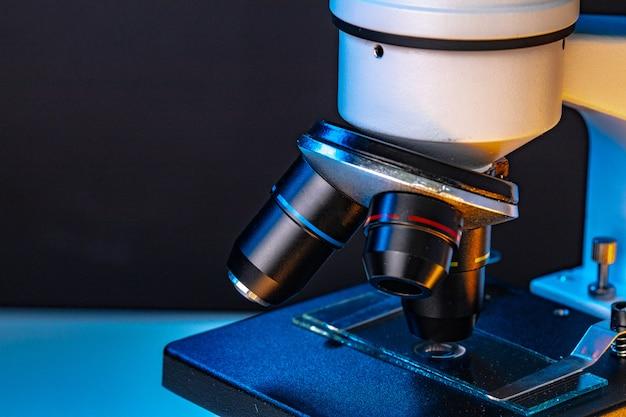 Il microscopio con le lenti si chiude su contro la parete scura