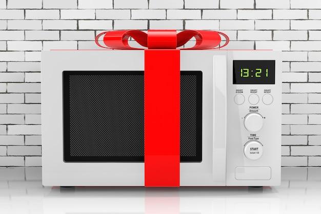 Regalo del forno a microonde con il nastro rosso e l'arco davanti al muro di mattoni. rendering 3d