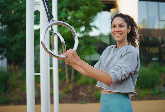 Metà donna adulta che fa esercizio su un tappetino all'aperto nel parco di allenamento della città, concetto di stile di vita sano.