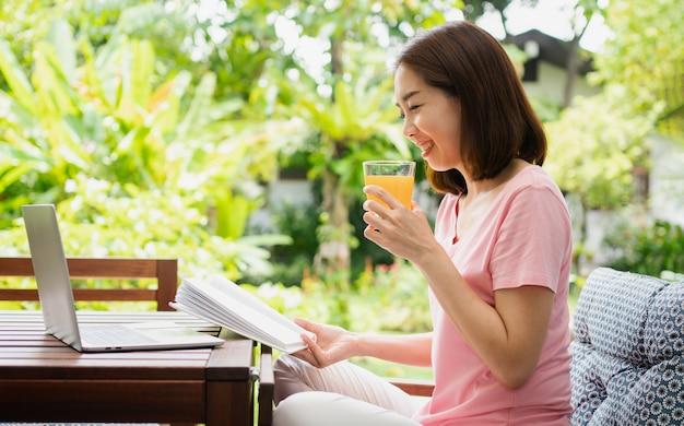 Donna asiatica di mezza età che legge un libro e tiene il bicchiere di succo d'arancia in casa. concetto di assistenza sanitaria e mangiare sano