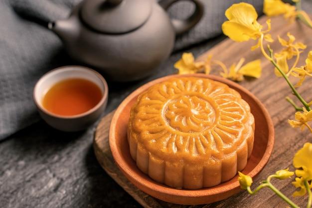 Mid-autumn festival cibo tradizionale concetto - bella torta di luna sul tavolo di ardesia nera con tè, stampo per pasticceria, fiore, primo piano, spazio copia