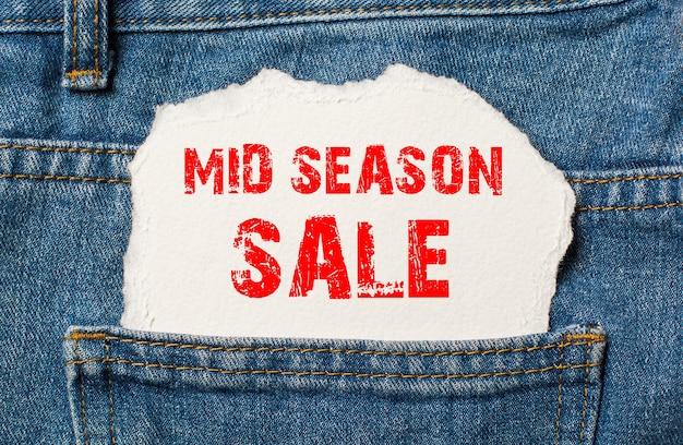Saldi di mezza stagione su carta bianca nella tasca dei jeans blu denim