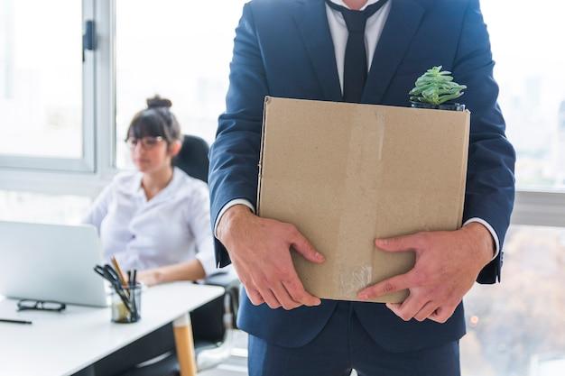 Metà di sezione dell'uomo d'affari che porta la scatola di cartone di roba per il nuovo posto di lavoro