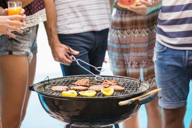 Metà di sezione di amici che preparano il barbecue
