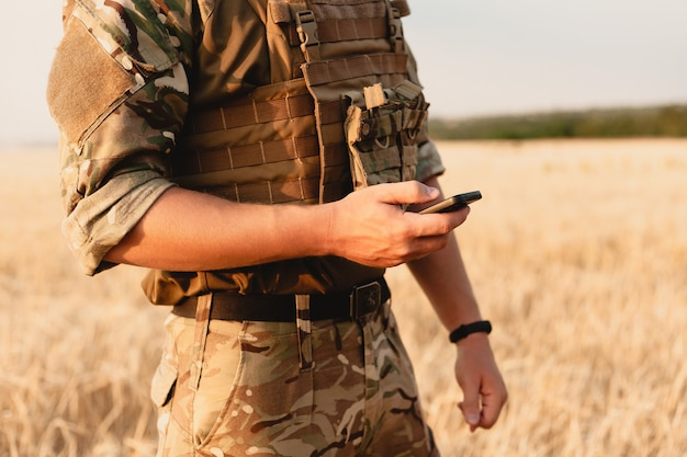 Sezione centrale del soldato militare che utilizza il telefono cellulare nel campo di addestramento