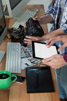 Metà di sezione di fotografi che lavorano alla scrivania