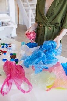 Ritratto di metà sezione della donna moderna che ordina i rifiuti di plastica a casa prima del riciclaggio