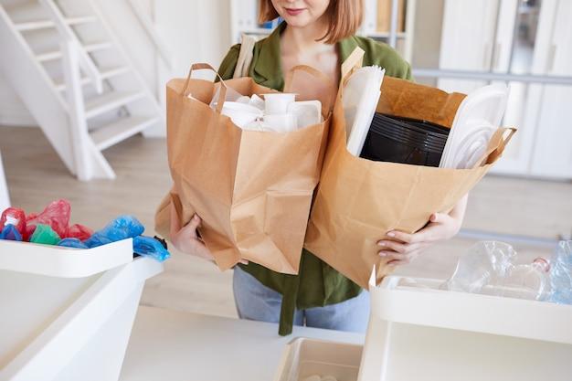 Ritratto di metà sezione della giovane donna moderna che tiene i sacchetti di carta con oggetti di plastica mentre smistano i rifiuti a casa