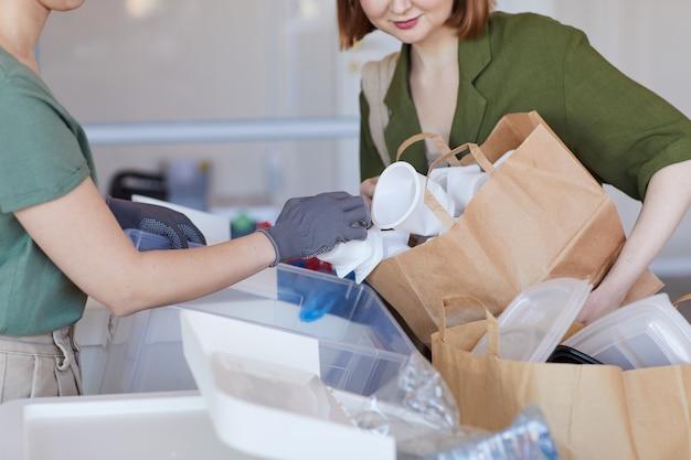 Ritratto di metà sezione di due persone che ordinano oggetti di plastica a casa, pronti per il riciclaggio