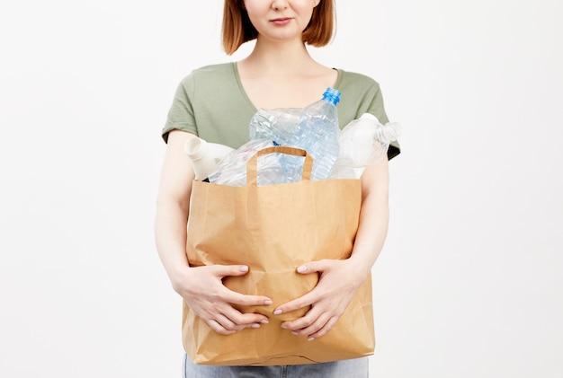 Ritratto a metà sezione di una donna irriconoscibile che tiene il sacchetto di carta con bottiglie di plastica mentre si trovava isolato, raccolta differenziata e concetto di riciclaggio