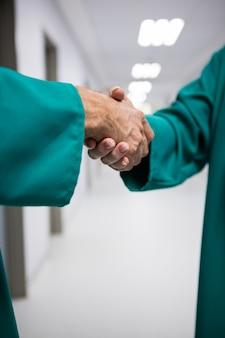 Metà di sezione di chirurghi che si stringono la mano in corridoio