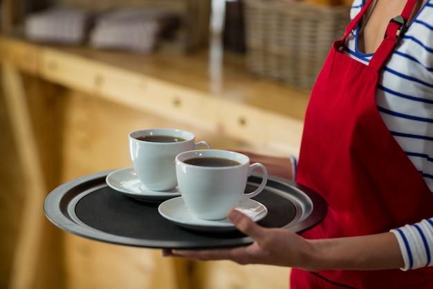 Mezza sezione della cameriera in piedi con una tazza di caffè