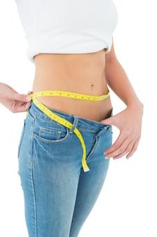 Metà di sezione di una donna che misura vita in un jeans di grandi dimensioni