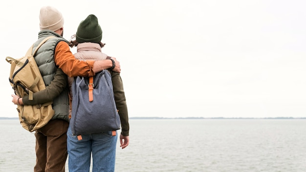 Coppia a metà tiro che abbraccia guardando il mare