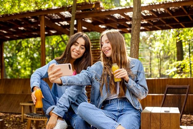 Amici a metà tiro con bottiglie di succo fresco che prendono selfie