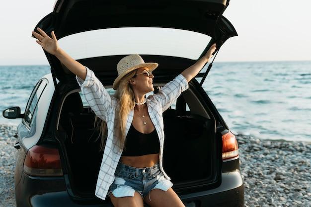 Metà di colpo donna felice in piedi nel bagagliaio di un'auto con bottiglia di succo