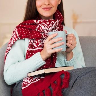 Donna felice a metà colpo con sciarpa e tazza