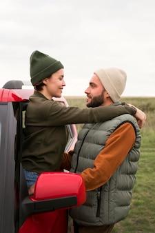 Donna a metà tiro che esce dall'auto dalla finestra e abbraccia l'uomo