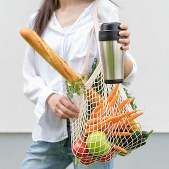 Metà donna del colpo che tiene borsa riutilizzabile e thermos fuori
