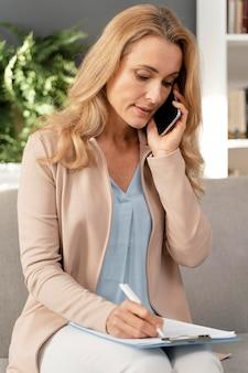 Terapista della donna del colpo medio che parla sul telefono