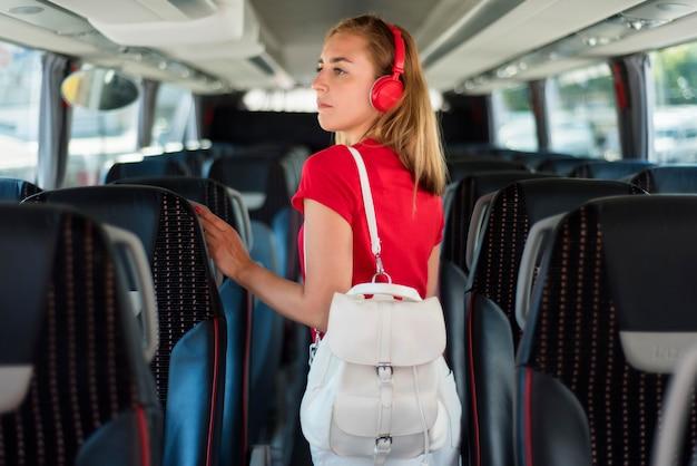 Donna a metà tiro con lo zaino in autobus