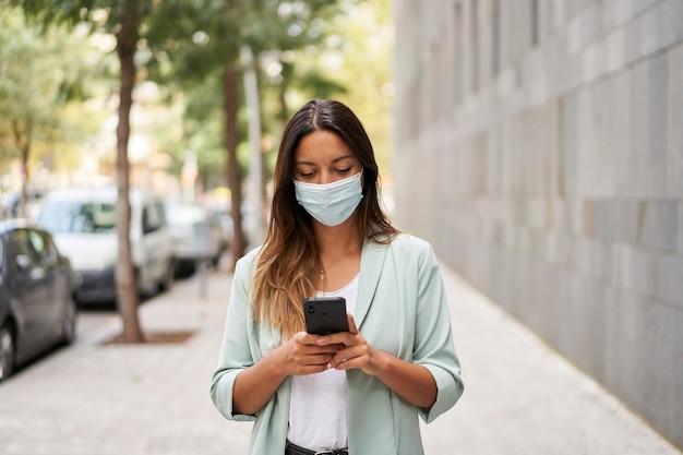 Metà colpo di una donna che lavora in una città utilizzando uno smartphone. indossa la maschera per la pandemia di coronavirus. è di fronte alla telecamera.