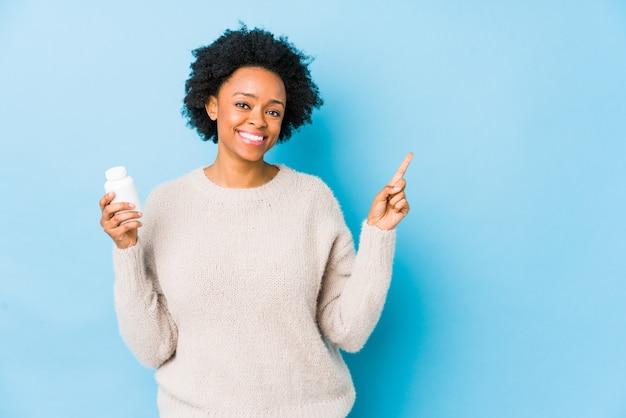 Donna afroamericana di medio evo che tiene una bottiglia della vitamina che sorride allegramente indicando con l'indice via.