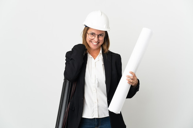 Donna dell'architetto di mezza età con il casco e che tiene le cianografie sopra la risata isolata della parete