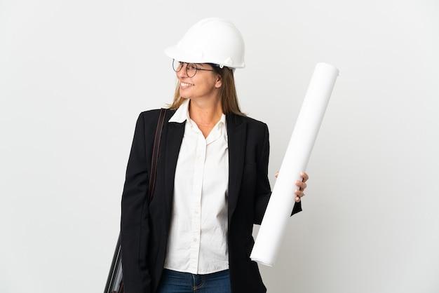 Donna dell'architetto di mezza età con il casco e che tiene le cianografie sopra la parete isolata che osserva al lato e che sorride
