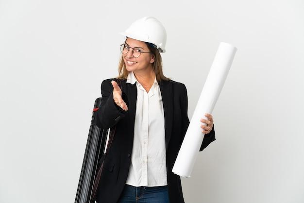 Donna dell'architetto di mezza età con il casco e che tiene le cianografie sopra la parete isolata che agitano le mani per chiudere un buon affare