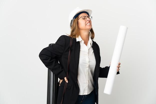 Donna dell'architetto di mezza età con il casco e che tiene le cianografie sopra il muro isolato che soffre di mal di schiena per aver fatto uno sforzo