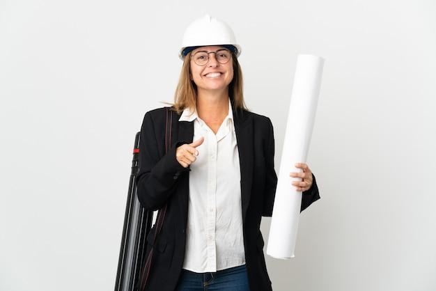 Donna dell'architetto di mezza età con il casco e che tiene i modelli sopra la parete isolata sorpresa e che indica davanti
