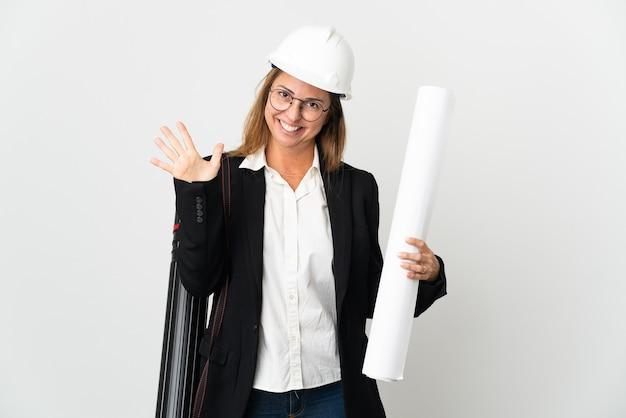 Donna dell'architetto di mezza età con il casco e le cianografie della holding isolate