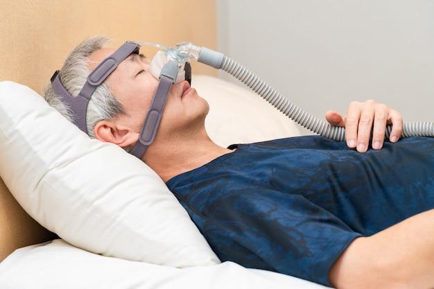 Uomo asiatico di mezza età che indossa copricapo cpap durante il suo sonno