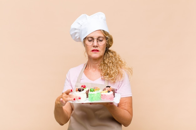 Donna del panettiere di mezza età che cucina torte