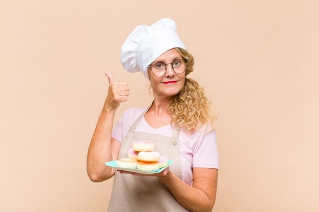 Donna panettiera di mezza età con ciambelle