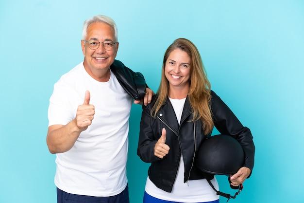 Coppia di motociclisti di mezza età con un casco da motociclista isolato su sfondo blu che fa un gesto di pollice in alto perché è successo qualcosa di buono