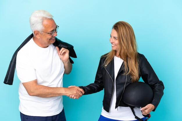 Coppia di motociclisti di mezza età con un casco da motociclista isolato su sfondo blu, stretta di mano dopo un buon affare