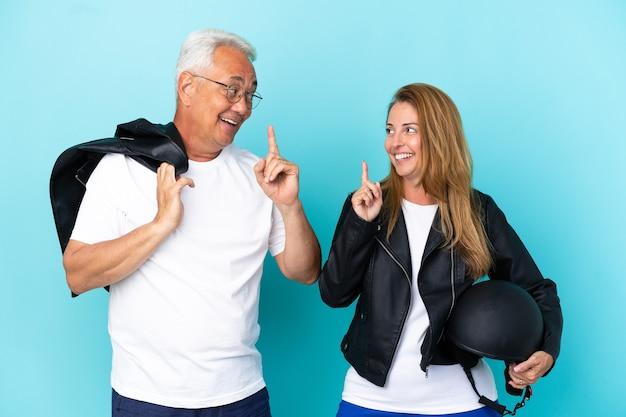 Coppia di motociclisti di mezza età con un casco da motociclista isolato su sfondo blu con l'intenzione di realizzare la soluzione mentre si solleva un dito