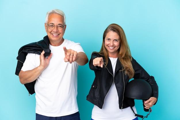 Coppia di motociclisti di mezza età con un casco da motociclista isolato su sfondo blu punta il dito contro di te con un'espressione sicura